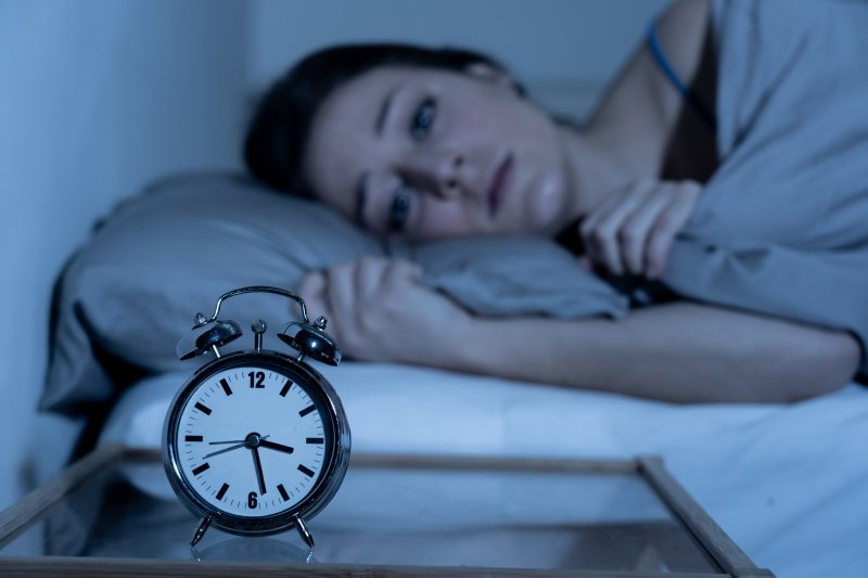 Anxious woman lying in bed staring at alarm clock