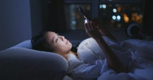 young woman using phone in bed