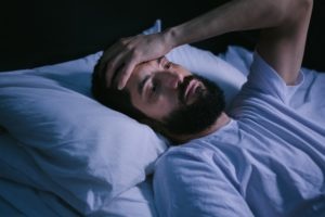 Exhausted man struggling with sleep apnea in Eugene