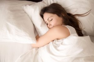 Woman in bed, going through stages of sleep